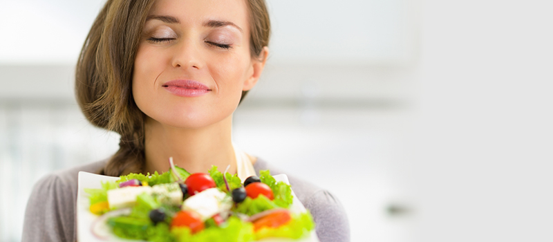 Portrait of young housewife enjoying fresh salad
